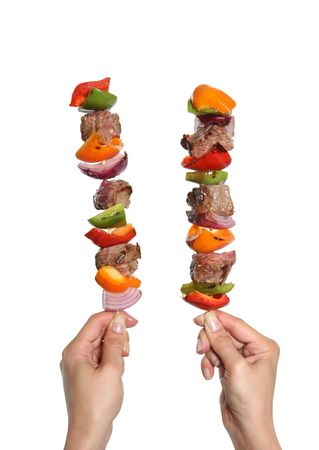 A woman holding two colorful kabobs with beef and vegetables