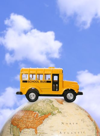 A yellow school bus driving on a globe