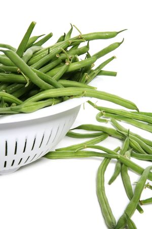 Fresh green beans in a strainer over white
