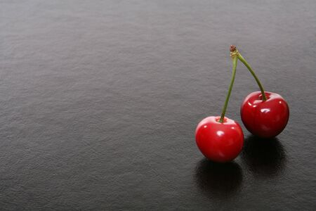 Two cherries over a black texteure