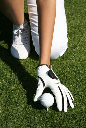 A woman golfer placing the golf ball on the tee Stock Photo - 1039854