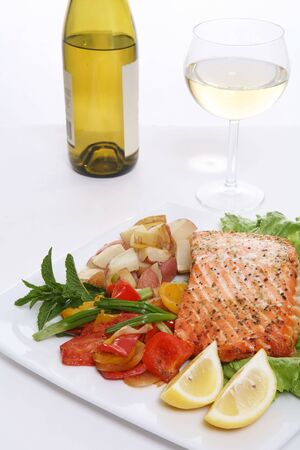 A baked salmon dinner with vegetables and potatoes and a glass of wine photo