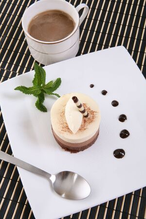 dainty: A chocolate mocha flavored cake tart dessert on a plate with coffee