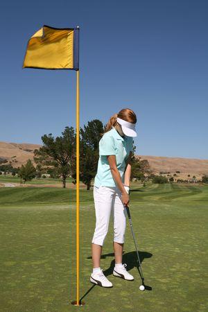 teen golf: Un golfista bonito de la mujer que pone para la igualdad en el curso del oro Foto de archivo