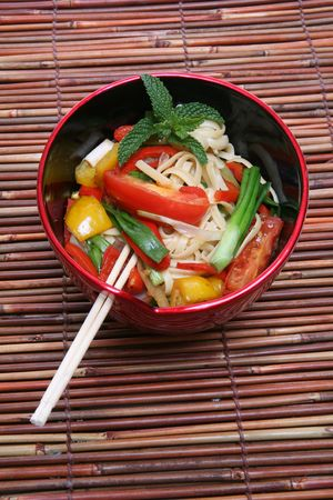 placemat: A colorful asian dish of noodles over a bamboo placemat Stock Photo