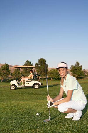 A pretty woman golfer ready to hit on the fairway Stock Photo - 1228797