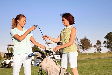 teen golf: Dos golfistas bonitos de las mujeres que seleccionan a un club del golf