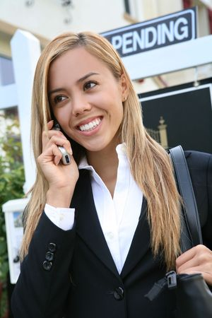A beautiful young real estate agent woman on the phone