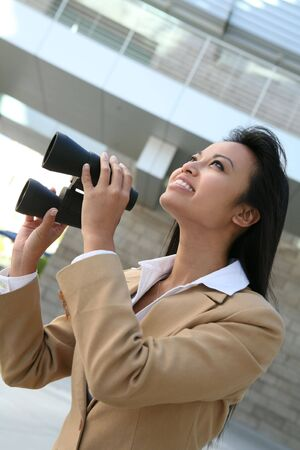 A pretty business woman with binoculars outside her office Stock Photo - 1318753