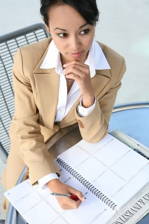 A pretty asian business woman writing in a calendar Stock Photo - 1327113