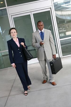 Two attractive business people leaving the company photo