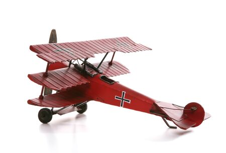 baron: An old antique model airplane over a white background