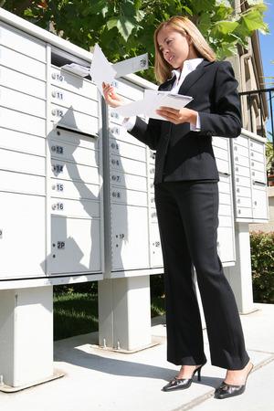 Een mooie jonge vrouw krijgt het bedrijfsleven de mail uit de mailbox