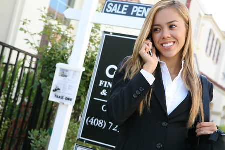 real business: A beautiful young real estate agent woman on the phone