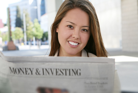 A pretty business woman reading the newspaper photo