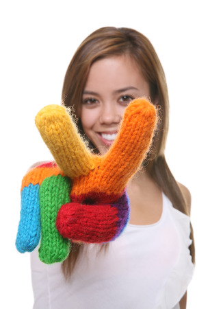 pacification: A pretty, young girl signaling a peace sign with rainbow gloves