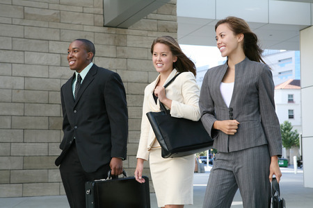 composed: An attractive business team walking composed of two women and a man Stock Photo