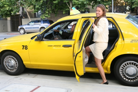 fare: A pretty business woman getting into a taxi cab Stock Photo