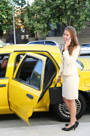 female driver: A pretty business woman outside a taxi cab on the phone