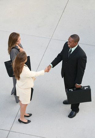 Three business professionals, man and women, shaking hands photo