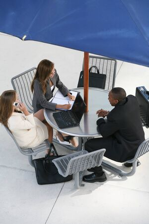 A business tean of two women and a man at a table photo