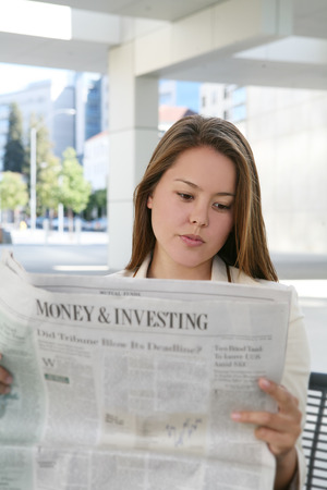 stockbroker: A pretty business woman reading the newspaper