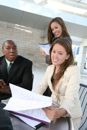A business tean of two women and a man discussing a project photo