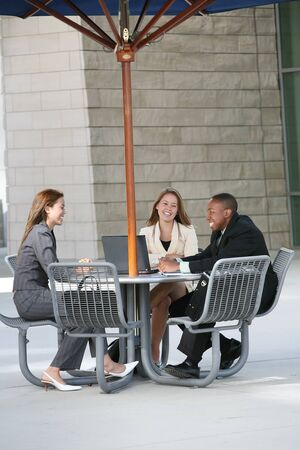 A business tean of two women and a man at a table Stock Photo - 1606013