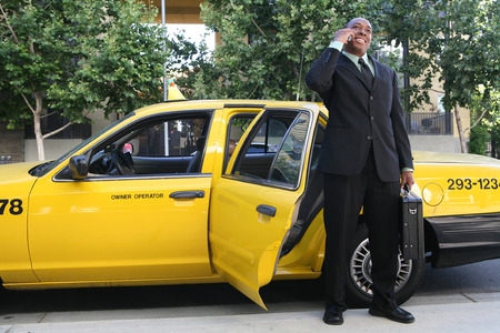A business man getting out of a taxi cab photo