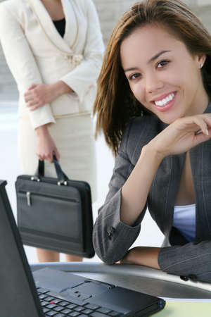 A pretty, young business woman smiling while working on laptop computer photo