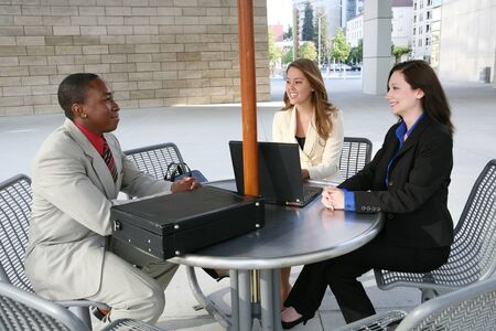 A business tean of two women and a man at a table Stock Photo - 1666905