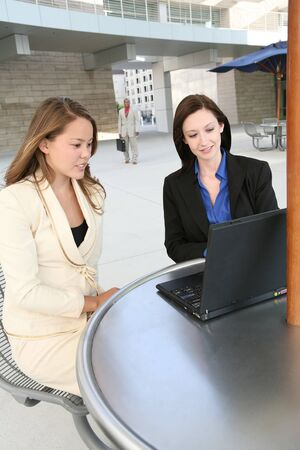 A pretty business team at an outside table on the computer photo