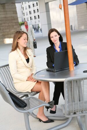 A pretty business team at an outside table on the computer Stock Photo - 1685270