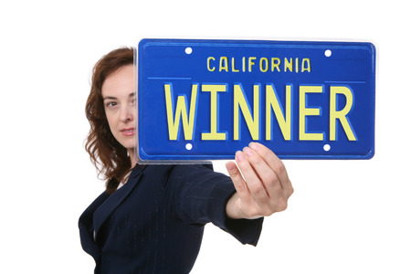 A pretty business woman holding a winner license plate