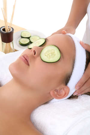 A beautiful young woman getting a facial at the spa