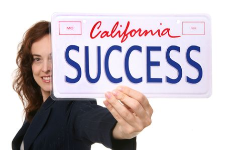 attainment: A pretty business woman holding a success license plate