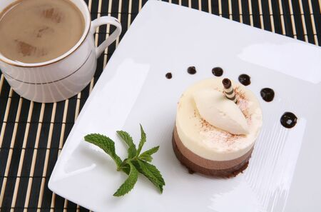 ambrosia: A chocolate mocha flavored cake tart dessert on a plate with coffee