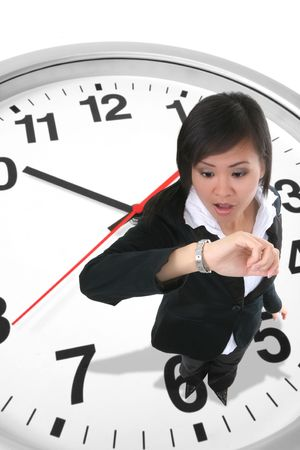 tardy: An attractive business woman standing on a clock and looking at her watch
