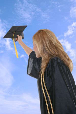 A woman thowing her graduation cap into the air Stock Photo