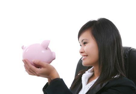 elated: A pretty asian business woman holding a piggy bank