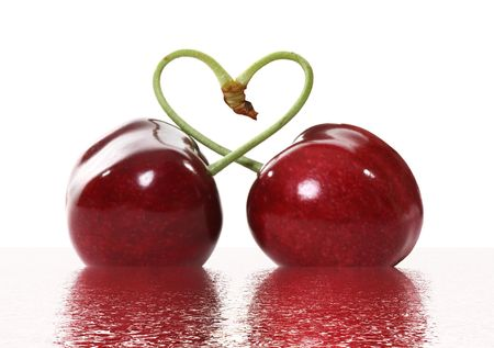 Two cherries tied together in a heart signifying love photo