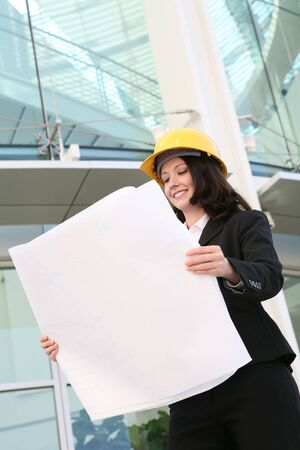 A pretty woman architect inspecting the blueprints photo