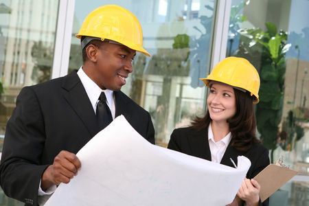 site: A young man and woman working as  architects on a building site Stock Photo