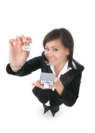 A real estate woman holding a key and house Фото со стока
