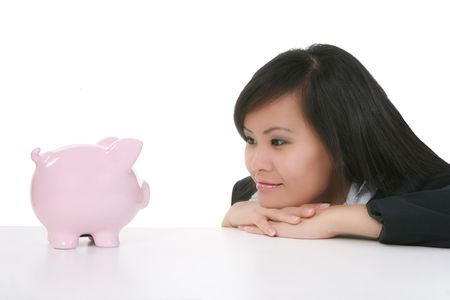 A pretty asian business woman staring at a piggy bank photo