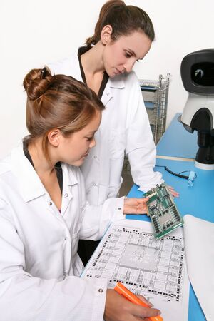 troubleshoot: Women computer technicians working on computer parts in the lab