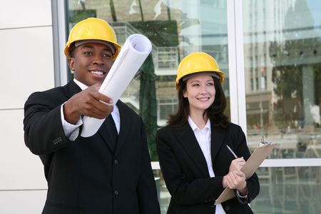 engineering clipboard: A young man and woman working as  architects on a construction site Stock Photo
