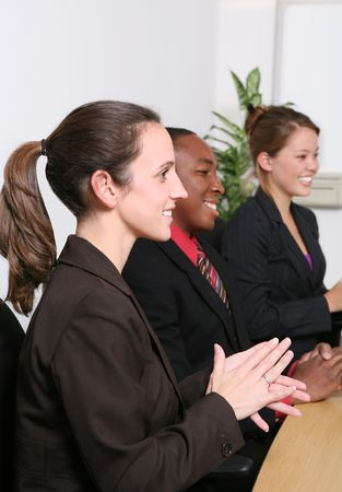 An attractive business team clapping in the office at presentation photo