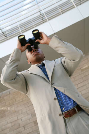 A business man looking through binoculars at his company photo