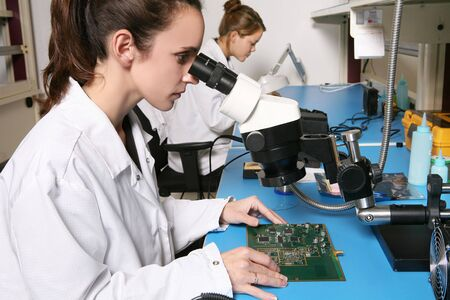 technical assistant: A pretty, young computer technician examining a printed circuit board with a m icroscope
